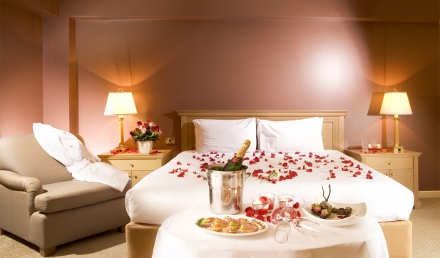 romantic-ambiance-on-bedroom-for-valentines-day-with-red-rose-petals-champagne-on-bucket-red-candle-wine-glass-pink-red-rose-on-white-flower-vase-beige-framed-bed-brown-coach-white-sheet